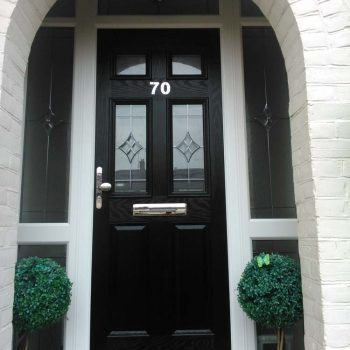 Black composite door with glazed square panels and decorative glass