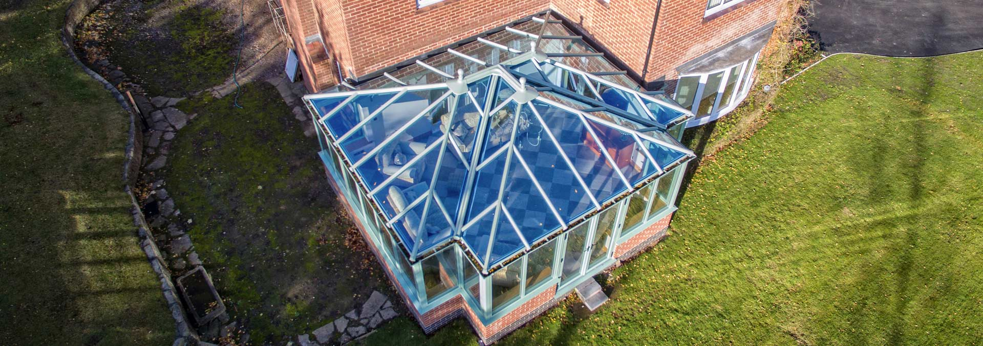 Large t-shape custom built conservatory with glass roof