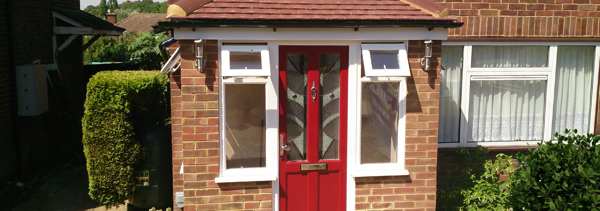 Brick porch installation with red door and casement windows