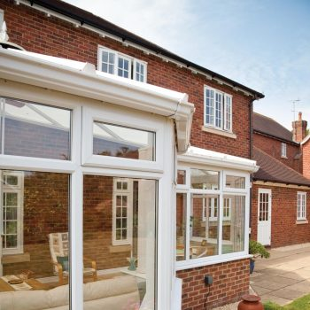 P-shape custom conservatory with double glazed windows and brick base