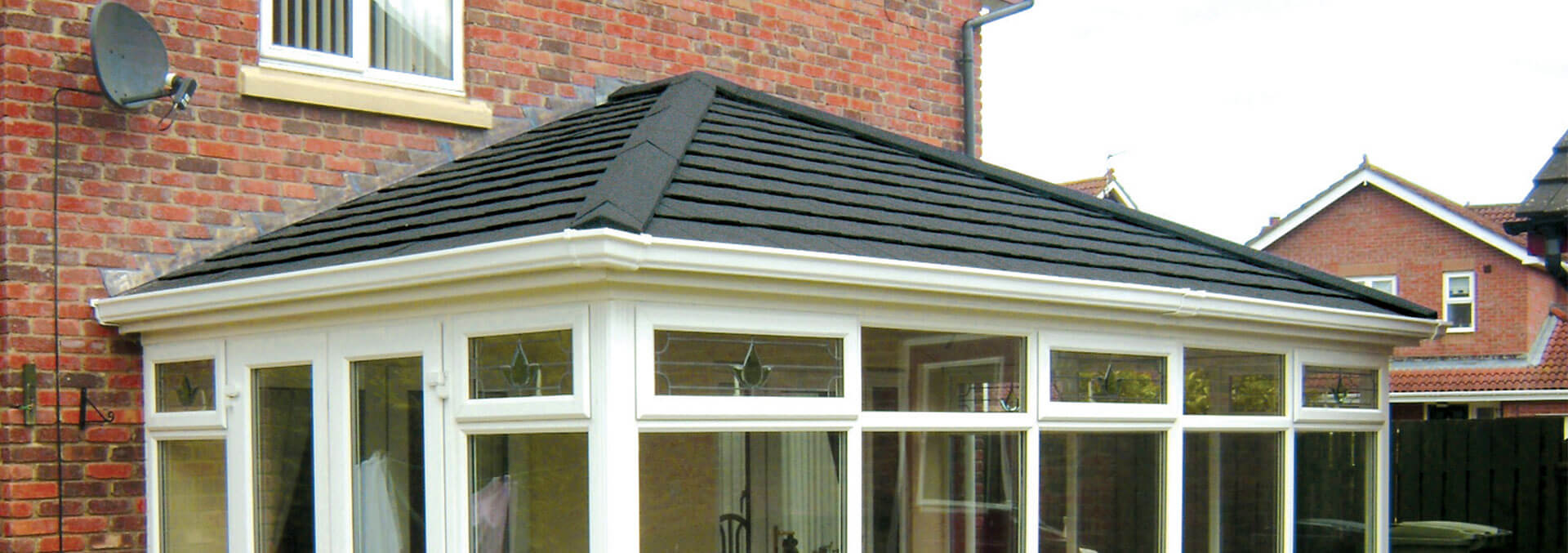 Large uPVC conservatory with grey tiled roof